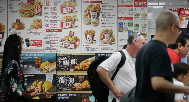 FILE - This Aug. 24, 2017 file photo, shows a KFC menu with calorie counts in New York. The Trump administration is moving ahead with a law from the Obama years that will require calorie counts to appear on foods served at restaurants, supermarkets, convenience stores and pizza delivery chains nationwide. The FDA posted recommendations Tuesday, Nov. 7, 2017 to help businesses comply with the law. (AP Photo/Bebeto Matthews)