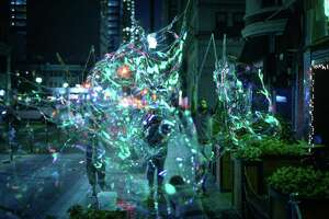 """The collaborative CRITT Project will perform """"Burst,"""" a piece involving dance and massive bubbles, on a grassy slope near Market Street as part of the 2017 edition of Luminaria."""
