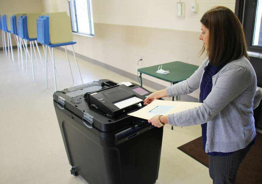 Voters in three Huron County municipalities and one school district faced decisions in Tuesday's election. Pictured, Bad Axe Deputy Clerk Melissa Carriveau feeds a ballot through one of the new voting machines that made their debut in the county. Photo: Seth Stapleton/Huron Daily Tribune