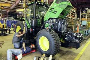 Alamo Industrial employees modify a John Deere tractor at the company's Seguin manufacturing plant. Seguin-based Alamo Group, the parent company of Alamo Industrial, recently saw a strike at an Ohio facility end after contract negotiations were successful.