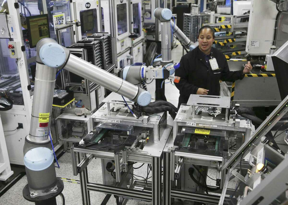 Meghan Escalante works among several automated robotic arms at Continental's Seguin manufacturing plant.