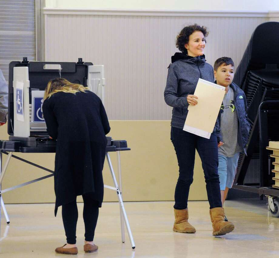 At center, Joan Franzino, holds her ballot as she walks with her son, Kingsley, 11, at the District 9 polling place during the election at the Western Greenwich Civic Center in the Glenville section of Greenwich on Tuesday. Photo: Bob Luckey Jr. / Hearst Connecticut Media / Greenwich Time