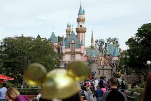 FILE - In this Jan. 22, 2015, file photo, visitors walk toward the Sleeping Beauty's Castle in the background at Disneyland Resort in Anaheim, Calif. Four prominent film critics groups announced Nov. 7, 2017, they will bar Walt Disney Co. films from receiving awards consideration over the company's decision to bar the Los Angeles Times from advance screenings of its films and access to its talent.  (AP Photo/Jae C. Hong, File)