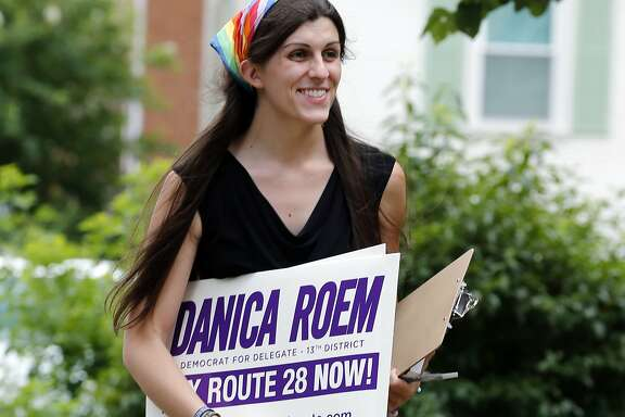 FILE - In this June 21, 2017, file photo, Democratic nominee for the House of Delegates 13th district seat Danica Roem brings campaign signs as she greets voters while canvasing a neighborhood in Manassas, Va. Roem, a former journalist, is challenging longtime incumbent Bob Marshall. If elected, Roem would be the state's first transgender representative. (AP Photo/Steve Helber, File)