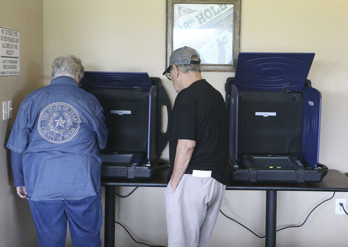 A man (right) gets ready to vote Tuesday at the Olmos Basin Golf Course in San Antonio.