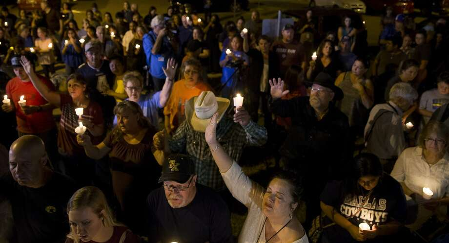 Susan Urban (in white), of Sutherland Springs, raises her hand in prayer with fellow community members during a vigil held at the Sutherland Springs post office across the street from First Baptist Church, Sunday, Nov. 5, 2017, in Sutherland Springs. ( Mark Mulligan / Houston Chronicle ) Photo: Mark Mulligan, Houston Chronicle