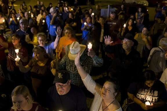 Susan Urban (in white), of Sutherland Springs, raises her hand in prayer with fellow community members during a vigil held at the Sutherland Springs post office across the street from First Baptist Church, Sunday, Nov. 5, 2017, in Sutherland Springs. ( Mark Mulligan / Houston Chronicle )