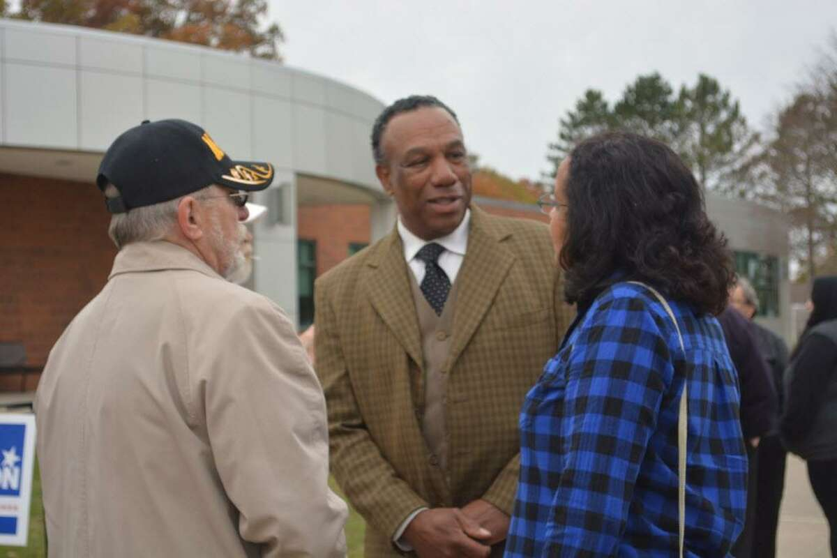 Democratic candidate for Cromwell selectman Myron Johnson greets voters Tuesday morning at Cromwell High School.