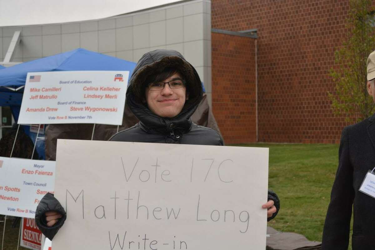 It was very cold out at the polls Tuesday during Cromwell's municipal elections. Here, write-in candidate for Board of Assessment Appeals Matthew Long campaigns at Cromwell High School late Tuesday morning.
