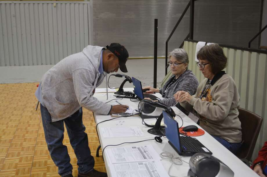 Voter Jesse Espinosa signs in to vote Tuesday morning at the Ollie Liner Center while election workers Jacquelyn Cornett and Diane Dowdy perform their duties. Photo: William Carroll, Plainview Herald