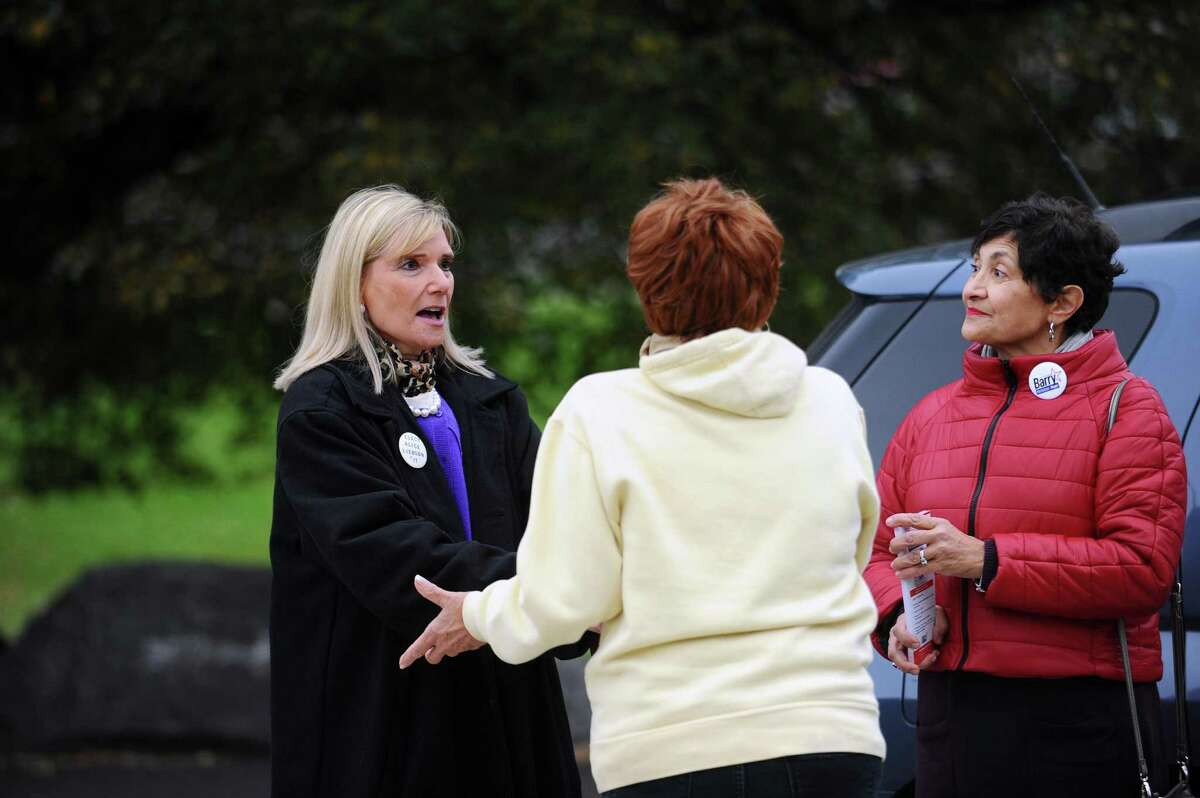 Board of Rep. member Alice Liebson (D-11), left, shakes hands and talks with a voter outside First Presbyterian School on Bedford Avenue in Stamford, Conn. on Tuesday, Nov. 7, 2017.