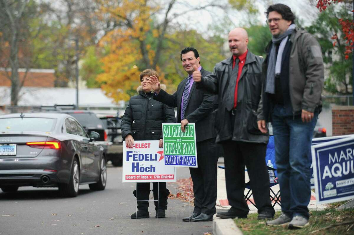 From left, Mary Fedeli, Sal Gabriele, Marc Aquila and David Michel wave to voters as they enter the parking lot of Springdale School in Stamford, Conn. on Tuesday, Nov. 7, 2017. Fedeli is running to retain her position on the Board of Reps., Gabriele is running to retain his position on the Board of Finance, Aquila is running for Board of Reps. and Michel is a volunteer for Reform Stamford.