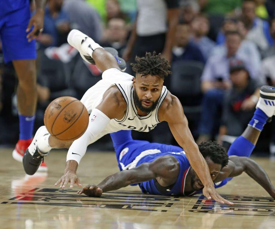 Patty Mills #8 of the San Antonio Spurs dives for a loose ball in front of Patrick Beverley #21 of the Los Angeles Clippers from Spurs
