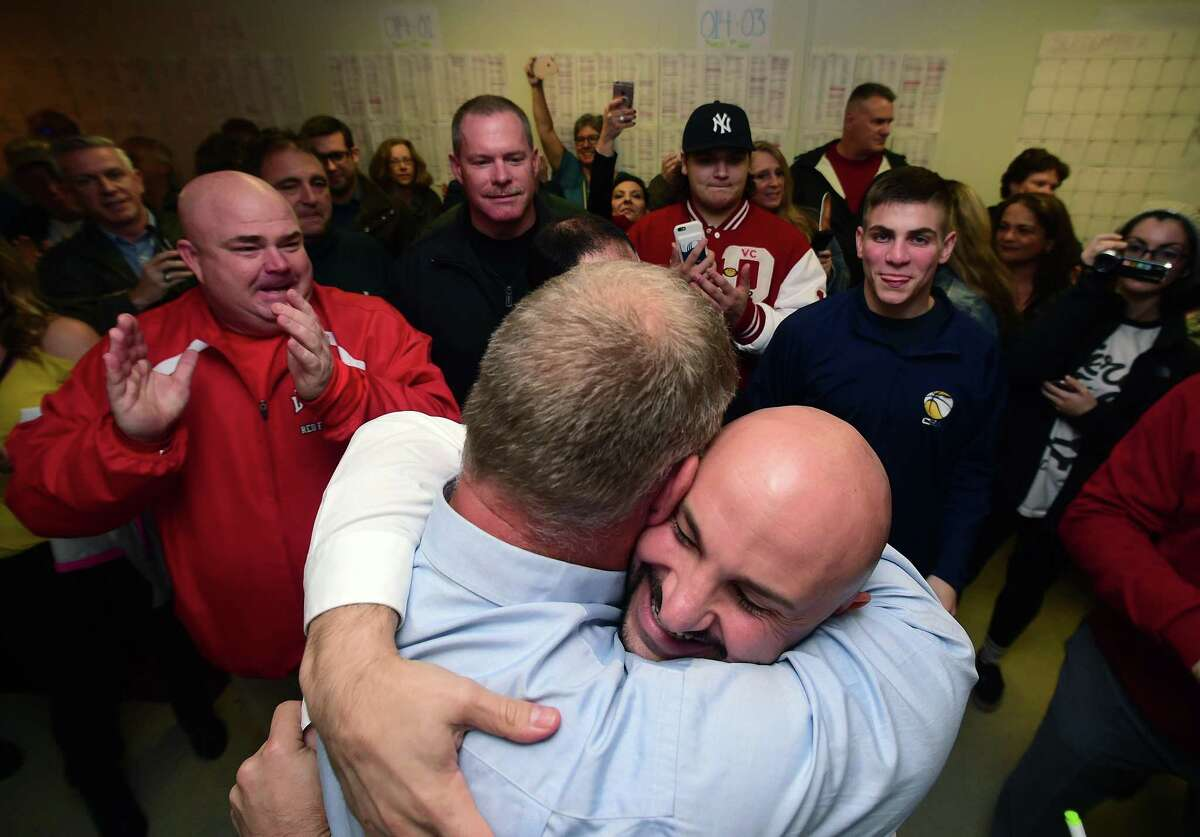 Rich Dziekan (center left) hugs campaign manager Andrew Baklik at his headquarters in Derby after results showed Dziekan as the winner in the Derby mayoral race on November 7, 2017.