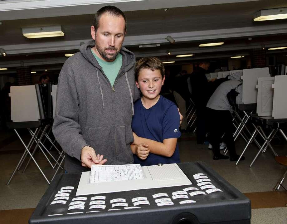 James Estabrook and son, Robby. take part in Election Day. Photo: Derek Torrellas