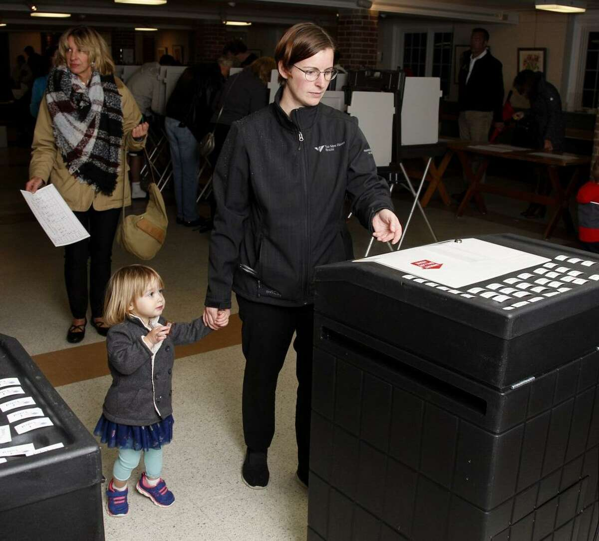 Kim Pont and daughter, Winter, age 2, vote at Clinton Town Hall Tuesday.