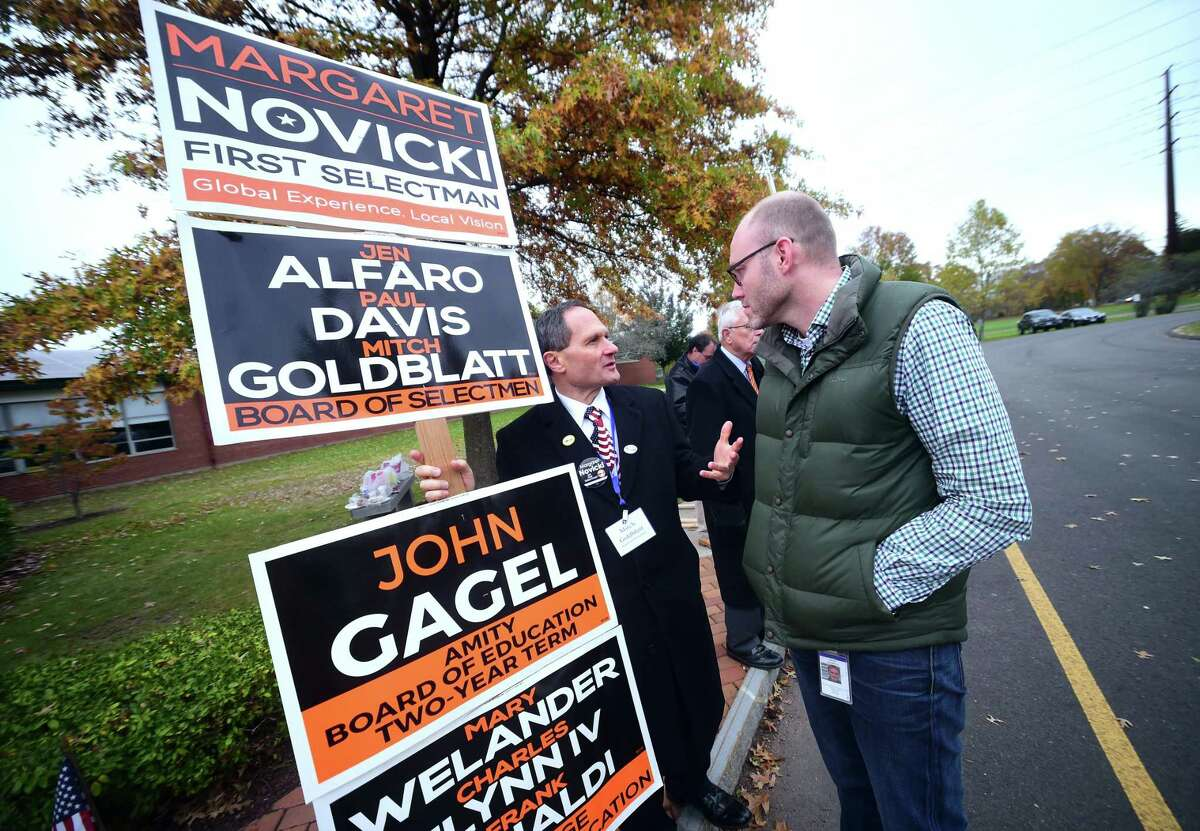 Board of Selectmen candidate Mitch Goldblatt (left) speaks with David Hudspeth outside of a polling place at the High Plains Community Center in Orange Tuesday.