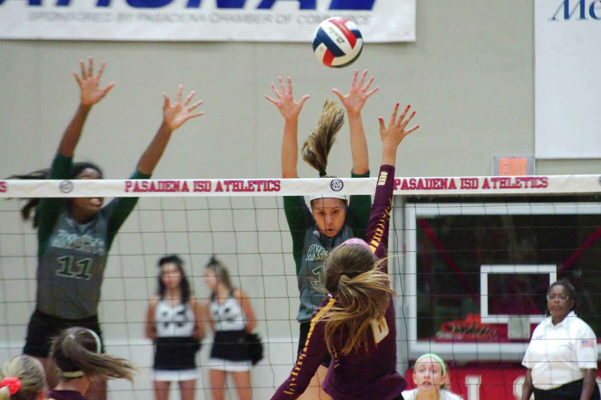Clear Falls' Rachel Brown (11) and Clear Falls' Briana Garcia (12) go high to block a shot by Deer Park's Courtney Plocheck (6) Tuesday, Nov. 7 at Pasadena ISD Phillips Field House.