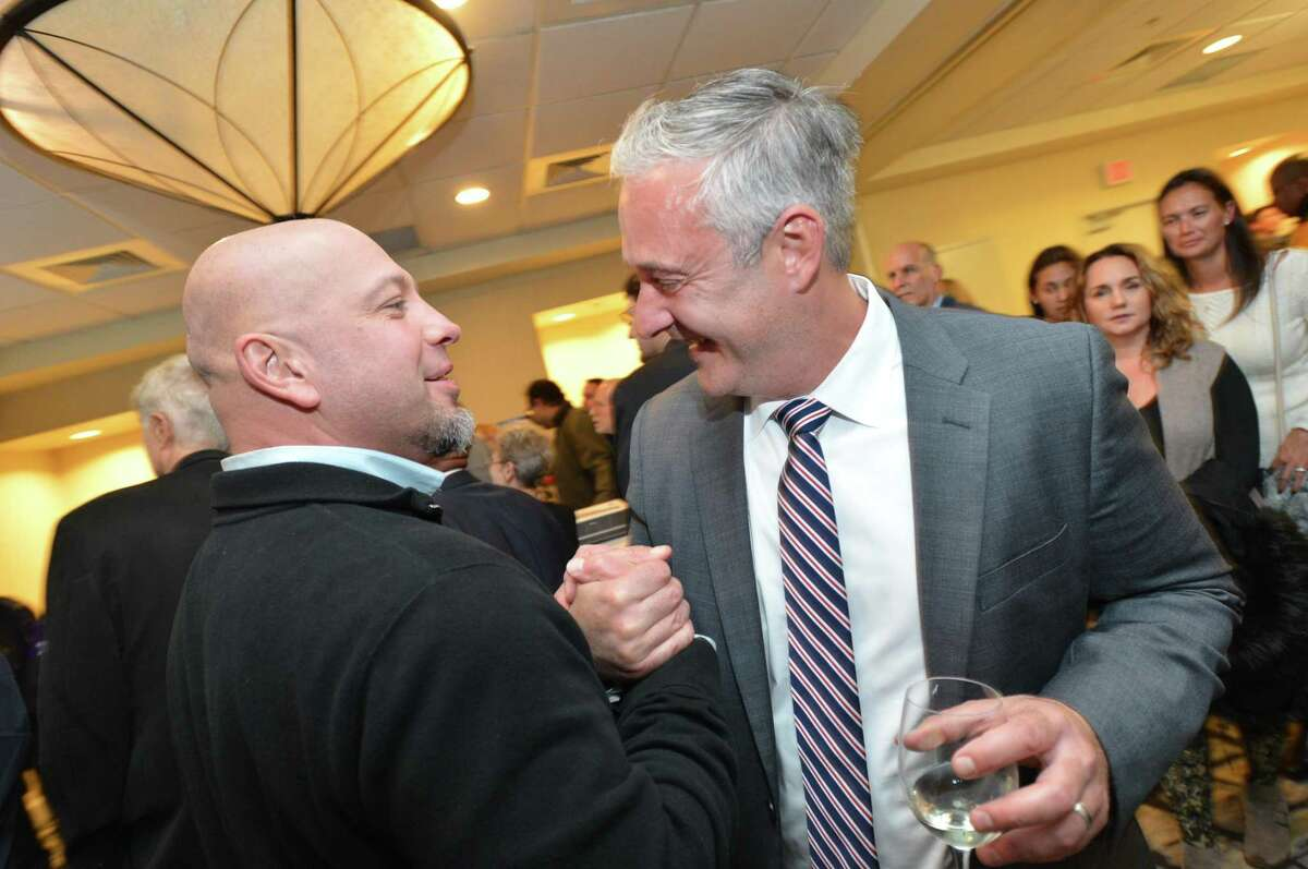 John Kydes celebrates his win in District C councilman seat with George Tsiranides in District D during a celebration of the Democrats wins on election day, Tuesday November 7, 2017 in Norwalk Conn.
