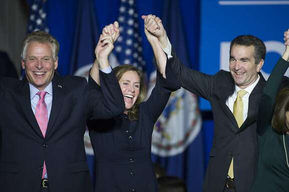 Virginia Gov.-elect Ralph Northam, right, celebrates his election victory with Virginia Gov. Terry McAuliffe and his wife Dorothy at the Northam For Governor election night party at George Mason University in Fairfax, Va., Tuesday, Nov. 7, 2017. (AP Photo/Cliff Owen)