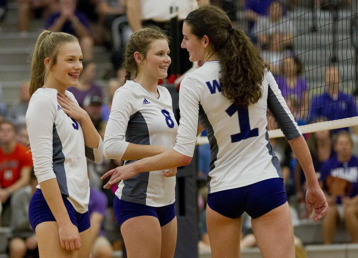 Willis outside hitter Kassy Perkins (3) jokes with middle blocker Makayla Bane (1) beside right side hitter Ashley Baldwin (8) during the fourth set of a Region III-5A quarterfinal match at Klein Collins High School, Tuesday, Nov. 7, 2017, in Spring.