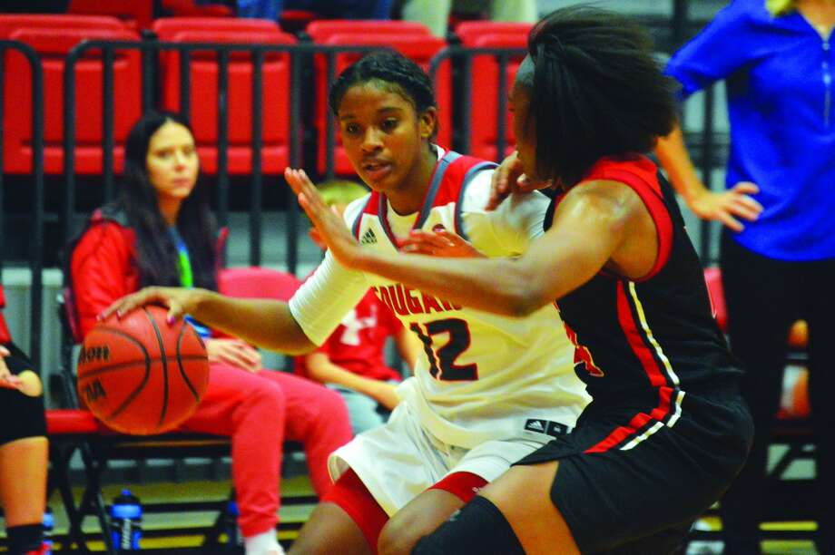 SIUE senior guard Lauren White, left, shields the ball away from an UMSL defender.
