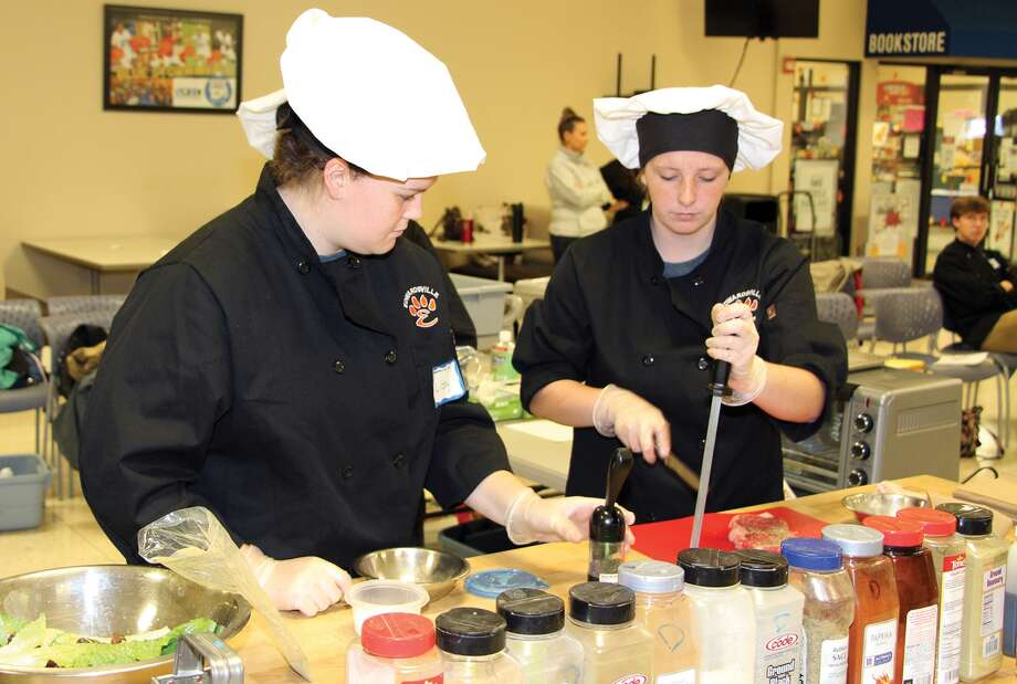 Edwardsville High School students  Libby Ward and Zoe Monroe sharpen knives before they starting cooking during the Platinum Chef Team Challenge held recently at the Southwestern Illinois College Sam Wolf Granite City Campus. Photo: For The Intelligencer