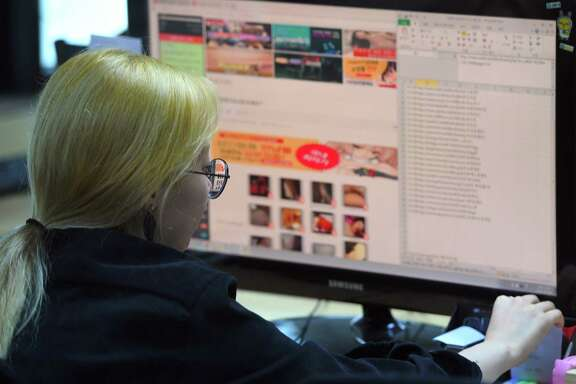 """This picture taken on July 24, 2017 shows an employee of Santa Cruise """"digital laundry"""" company monitoring a computer screen to find """"revenge porn"""" at the company in Seoul.  The company is tasked with taking down videos posted without consent -- including so-called """"revenge porn."""" In hyper-wired South Korea, 7,325 requests to have intimate videos removed from the internet were made in 2016, according to government figures, a sevenfold increase in only four years. / AFP PHOTO / JUNG Yeon-Je / TO GO WITH AFP STORY SKOREA-TECHNOLOGY-CRIME-GENDER,FEATURE BY JUNG HA-WONJUNG YEON-JE/AFP/Getty Images"""