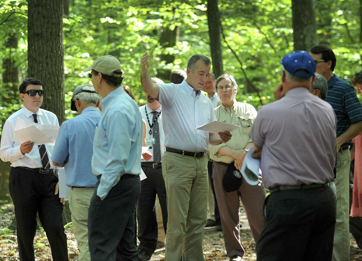 Joel Lindsay, center, with Ameresco Candlewood Solar LLC, leads a walking tour for the state Siting Council of the area where there is a proposal to build solar panels on Candlewood Mountain in New Milford on Sept. 26.