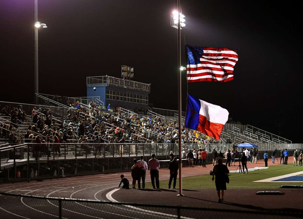 Flags fly at half mast during a memorial service for victims of the mass shooting that killed 26 people in Sutherland Springs, at the La Vernia High School in Texas on November 7, 2017. A gunman wearing all black armed with an assault rifle opened fire on a small-town Texas church during Sunday morning services, killing 26 people and wounding 20 more in the last mass shooting to shock the United States. / AFP PHOTO / MARK RALSTON (Photo credit should read MARK RALSTON/AFP/Getty Images)