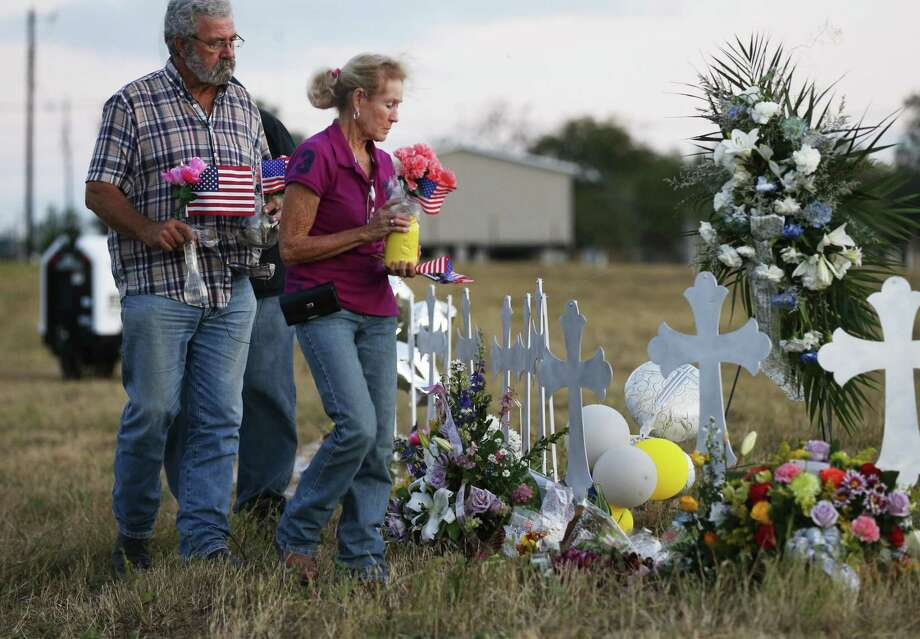 Sutherland Springs residents Rod and Judy Green bring flowers and flags to place along a row of crosses to mourn the victims of Sunday's shooting tragedy at First Baptist Church in Sutherland Springs, Texas on Tuesday, Nov. 7, 2017. (Kin Man Hui/San Antonio Express-News) Photo: Kin Man Hui, Staff / San Antonio Express-News / ©2017 San Antonio Express-News