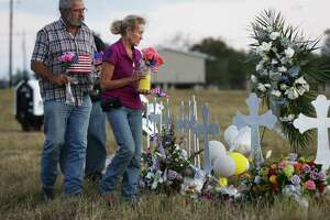 Sutherland Springs residents Rod and Judy Green bring flowers and flags to place along a row of crosses to mourn the victims of Sunday's shooting tragedy at First Baptist Church in Sutherland Springs, Texas on Tuesday, Nov. 7, 2017. (Kin Man Hui/San Antonio Express-News)