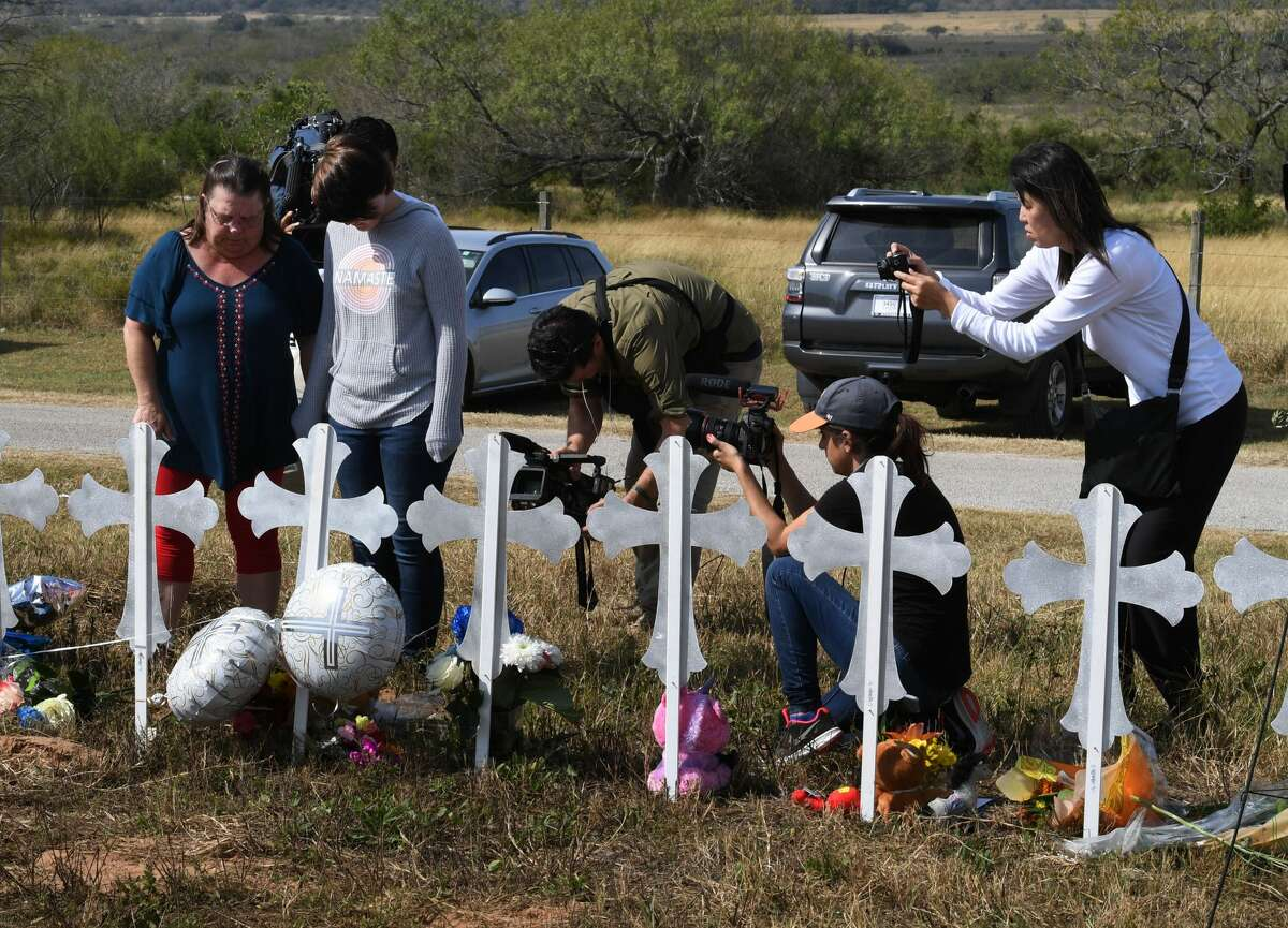 Belinda McLauren and Randi Ray Rivera pray surrounded by cameras after a mass shooting that killed 26 people in Sutherland Springs, Texas on November 7, 2017. A gunman wearing all black armed with an assault rifle opened fire on a small-town Texas church during Sunday morning services, killing 26 people and wounding 20 more in the last mass shooting to shock the United States. / AFP PHOTO / MARK RALSTON (Photo credit should read MARK RALSTON/AFP/Getty Images)