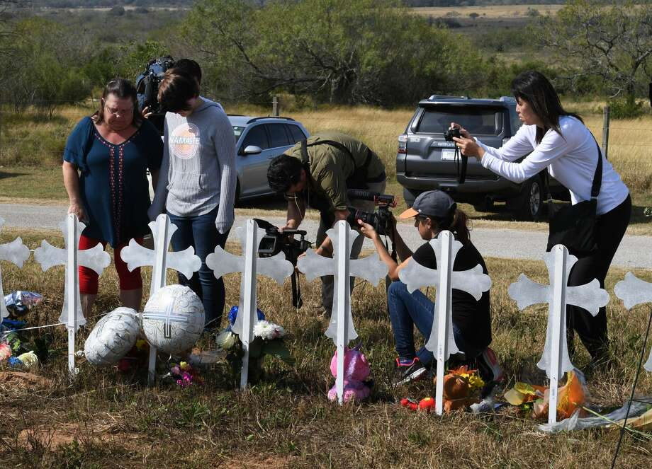 Belinda McLauren and Randi Ray Rivera pray surrounded by cameras after a mass shooting that killed 26 people in Sutherland Springs, Texas on November 7, 2017. A gunman wearing all black armed with an assault rifle opened fire on a small-town Texas church during Sunday morning services, killing 26 people and wounding 20 more in the last mass shooting to shock the United States. / AFP PHOTO / MARK RALSTON        (Photo credit should read MARK RALSTON/AFP/Getty Images) Photo: MARK RALSTON/AFP/Getty Images