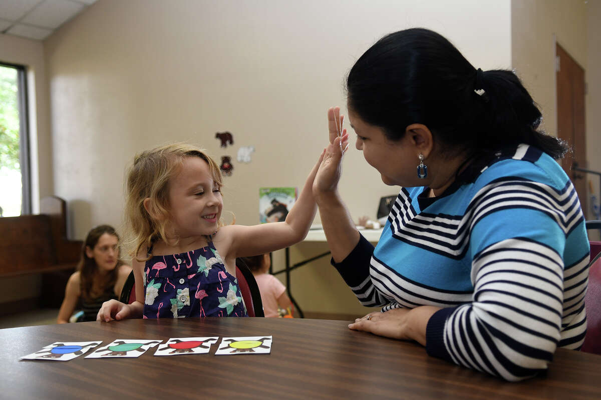 Adalyn Lyon, 3, left, gets a high-five from Akhila Bhat, Asst. Branch Librarian for Children's Services at Barbara Bush Branch Library, after completing a puzzle during a storytime at Holy Comforter Episcopal Church in Spring on Nov. 7, 2017. (Photo by Jerry Baker/Freelance)