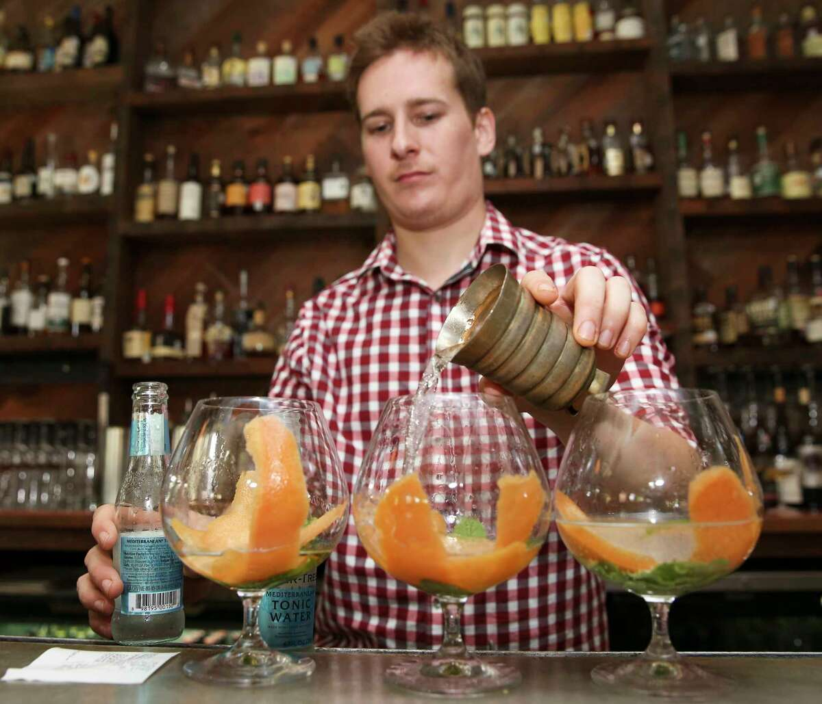 Coltivare bartender William Stewart makes three orders of gin and tonic, the most popular drink at the restaurant, at the bar Friday, June 9, 2017, in Houston.