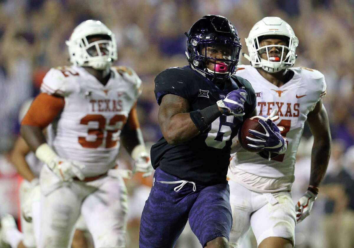 Darius Anderson (6) of the TCU Horned Frogs is pursued by Malcolm Roach (32) of the Texas Longhorns and DeShon Elliott (4) of the Texas Longhorns as he runs for a fourth quarter touchdown at Amon G. Carter Stadium on November 4, 2017 in Fort Worth, Texas. (Photo by Richard W. Rodriguez/Getty Images)