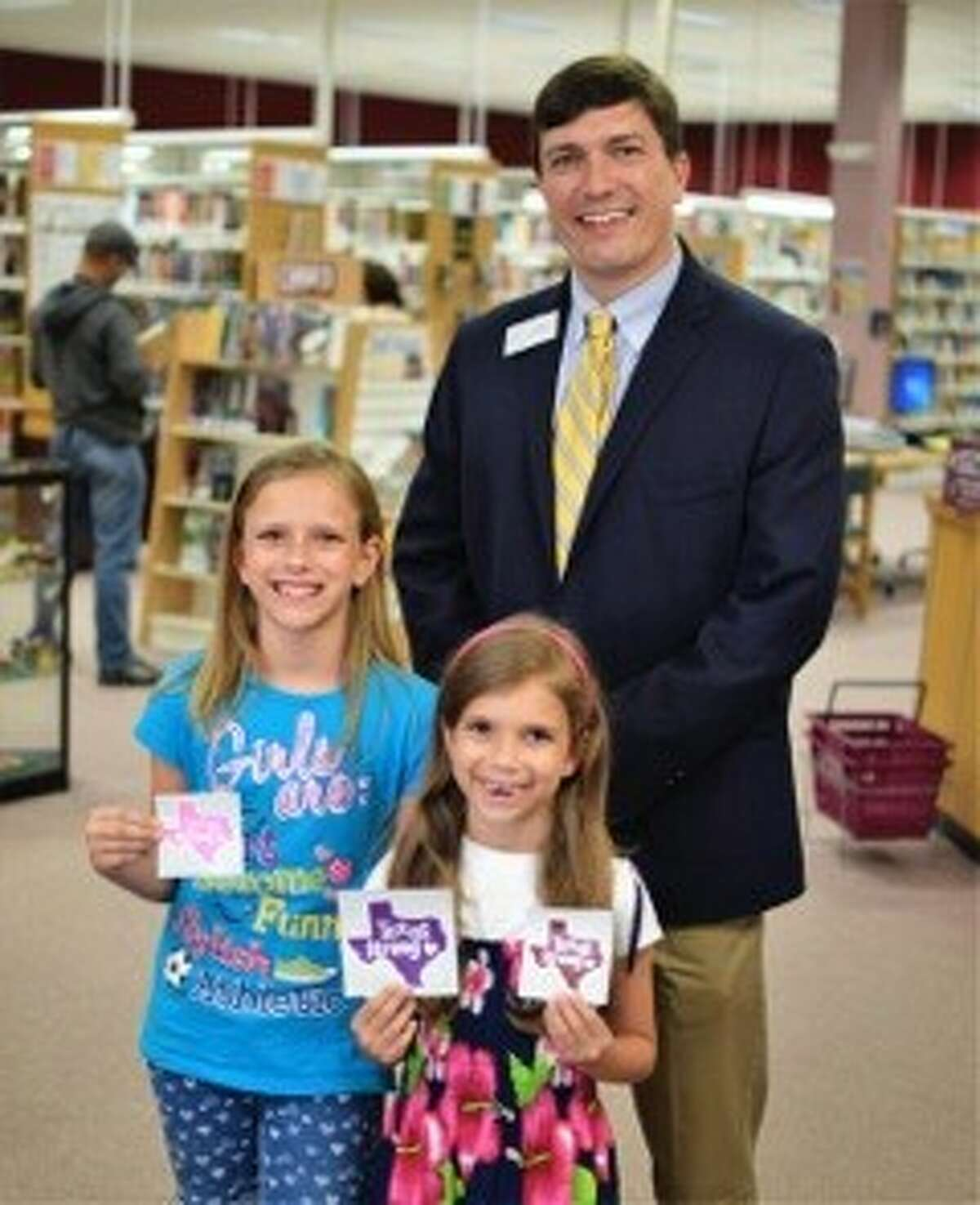 Hailey and London Ashton are pictured with Kingwood Library Branch Manager Ryan Fennell.