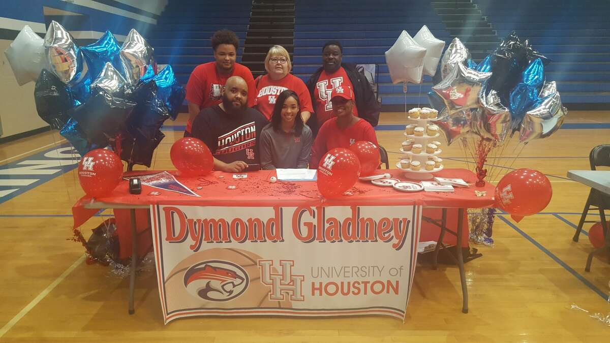 Clear Springs' Dymond Gladney is joined by family as she signs to play basketball at the University of Houston on Nov. 8, 2017.