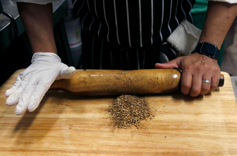 Chef Manish Tyagi uses a belan to crush spices for his tawa fish at August 1 Five restaurant. Photo: Liz Hafalia, The Chronicle