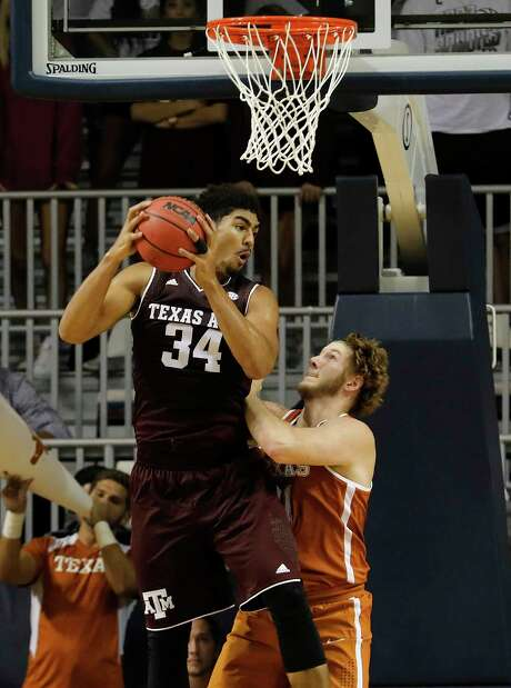 Texas A&M Aggies center Tyler Davis (34) grabs a rebound in front of Texas Longhorns forward Dylan Osetkowski (21) in the first half during the exhibition basketball game between the Texas Longhorns and the Texas A&M Aggies to benefit the Rebuild Texas Relief Fund at Tudor Fieldhouse in Houston, TX on Wednesday, October 25, 2017. Photo: Tim Warner, Freelance / Houston Chronicle