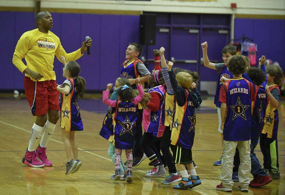 "File photo Harlem Wizards player Swoop ( Dwayne Simpson) dances with the Harlem Wiz Kids as they warm up for the game. The Roxbury Organization of Parents and Educators hosted a basketball game and school fundraiser against the Harlem Wizards at Westhill High School in Greenwich, Connecticut on Friday, Oct. 27, 2017. Professional boxer Chordale ""The Gift"" Booker, an alum of Roxbury, played alongside 20 educators and staff of the school. Photo: Matthew Brown / Hearst Connecticut Media / Stamford Advocate"