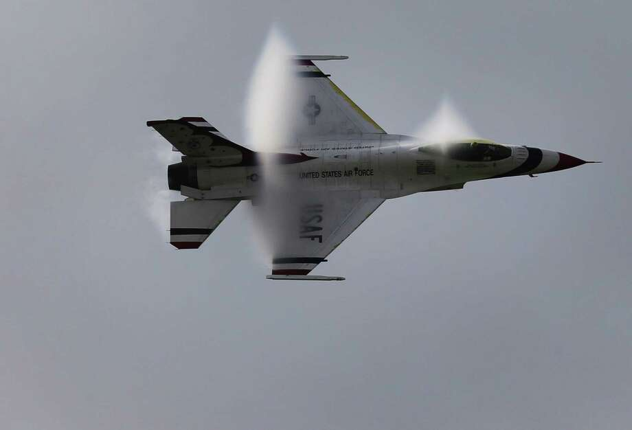 A U.S. Air Force Thunderbird generates a vapor cone as it zooms through the sky over San Antonio and Kelly Field for this weekend's JBSA Air Show and Open House 2017 on Thursday, Nov. 2, 2017. The Thunderbirds roared above the airfield's skies as one of the show's marquee performances. The show kicks off on Saturday to the public with static displays of various military aircraft from history to modern day. Several aerial demonstrations will take place along with the Thunderbirds. (Kin Man Hui/San Antonio Express-News) Photo: Kin Man Hui, Staff / San Antonio Express-News / ©2017 San Antonio Express-News