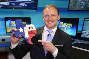 "KSAT-TV's weekday evening meteorologist Adam Caskey flashes one of his useful and kitschy handmade thermometers, which have become his trademark and landed him atop a national weathercaster ""cool"" list compiled by the Washington Post."