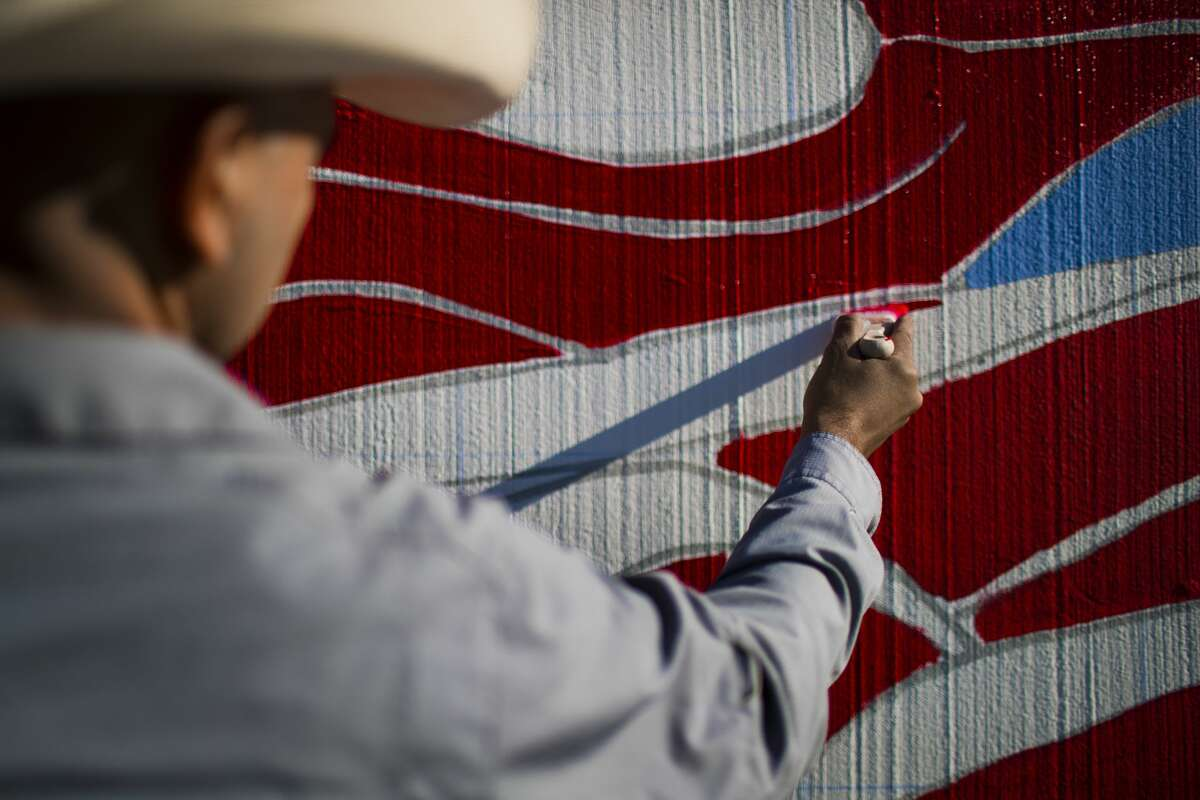 Gonzo247, Houston artist, works on the commissioned by Harris County to recreate Leo Tanguma's historic