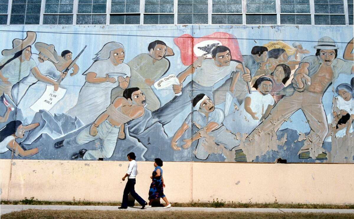 11/19/1987 - Pedestrians walk past mural titled