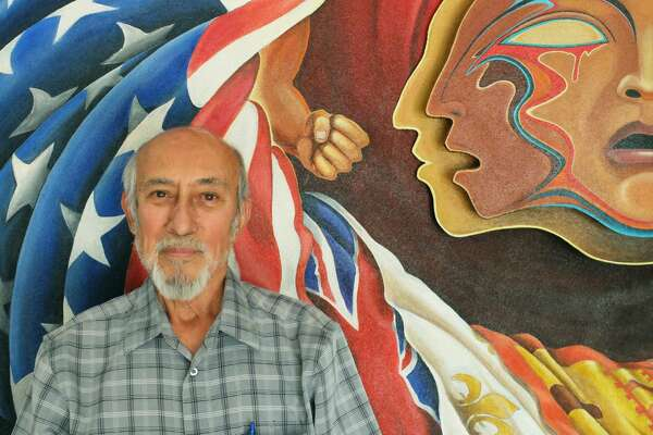 "Artist Leo Tanguma poses with the center section of his 64-foot mural""The Torch of Quetzalcoatl,"" which he keeps in his garage in Arvada, Colorado. The mural  was commissioned by the Denver Art Museum."