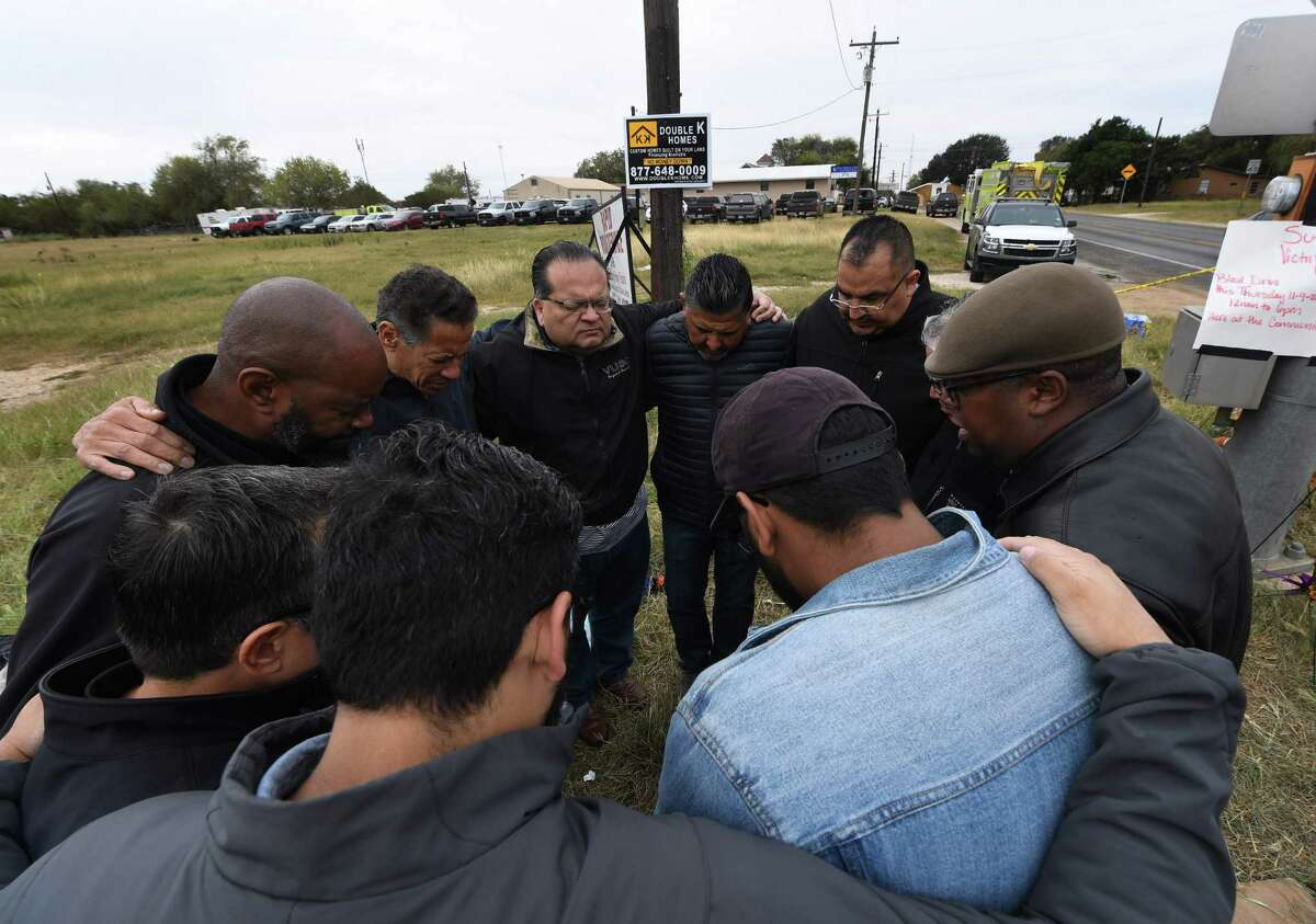 A group of 12 pastors from local churches, pray beside a memorial service for victims of the mass shooting that killed 26 people in Sutherland Springs, Texas on November 8, 2017. A gunman wearing all black armed with an assault rifle opened fire on a small-town Texas church during Sunday morning services, killing 26 people and wounding 20 more in the last mass shooting to shock the United States. / AFP PHOTO / MARK RALSTONMARK RALSTON/AFP/Getty Images