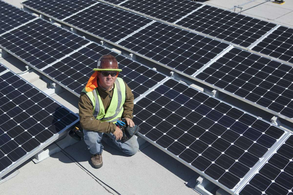 Worker sitting with solar panels outdoors