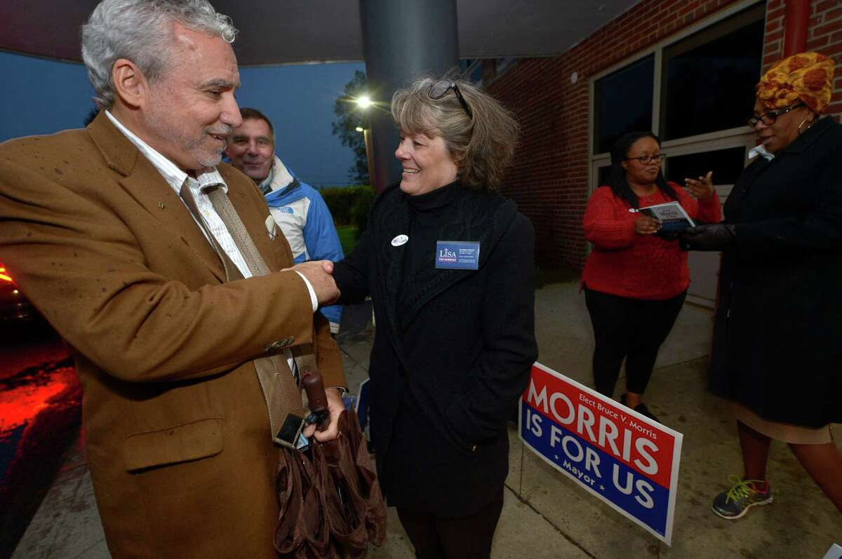 Johnny Cardamone greets Independent petition candidate for mayor Lisa Brinton as she campaigns outside Nathan Hale Middle School Tuesday, Nov. 8, in Norwalk.